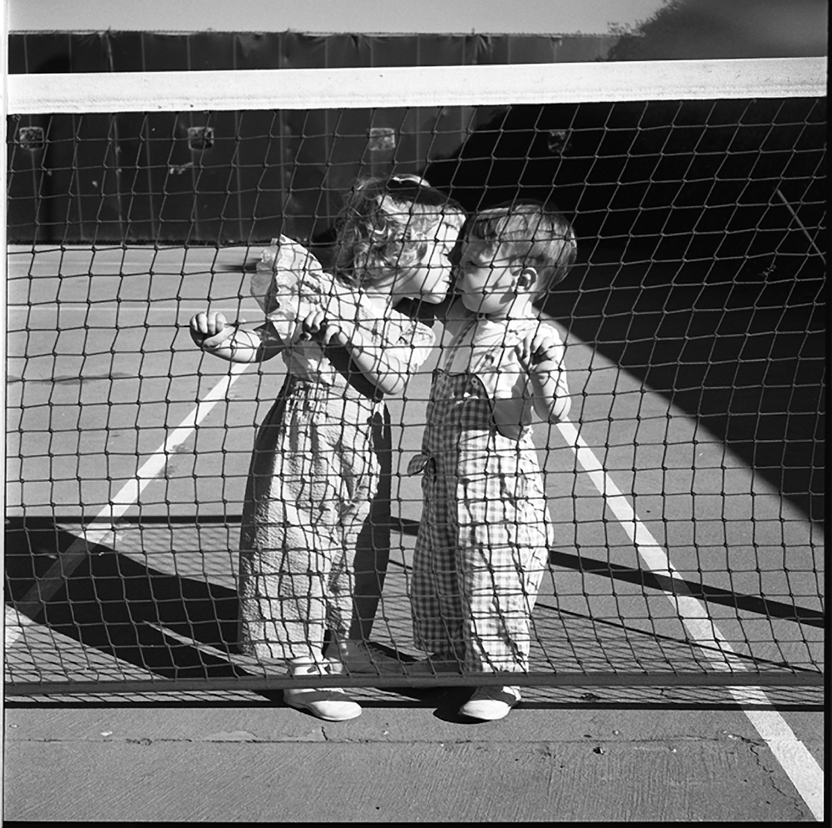 Vivian Maier, Two Children Kissing at Tennis Net, Los Angeles, August 1955