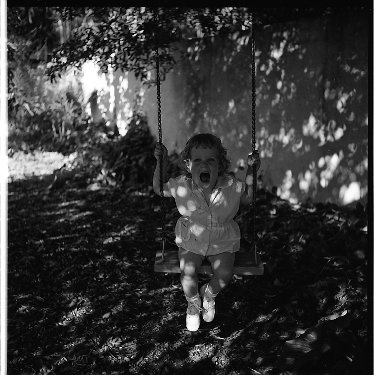 Vivian Maier, Little Girl Swinging in Shadows, Los Angeles, 1955